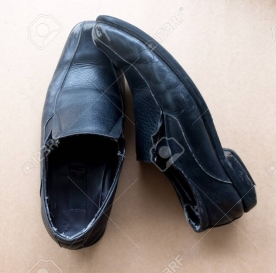 Old pair of used black leather shoes